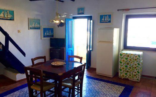 Sala di ingresso di un appartamento di Giglio Porto con tavolino di legno marrone, sedie. Di fronte una porta di ingresso di colore azzurro