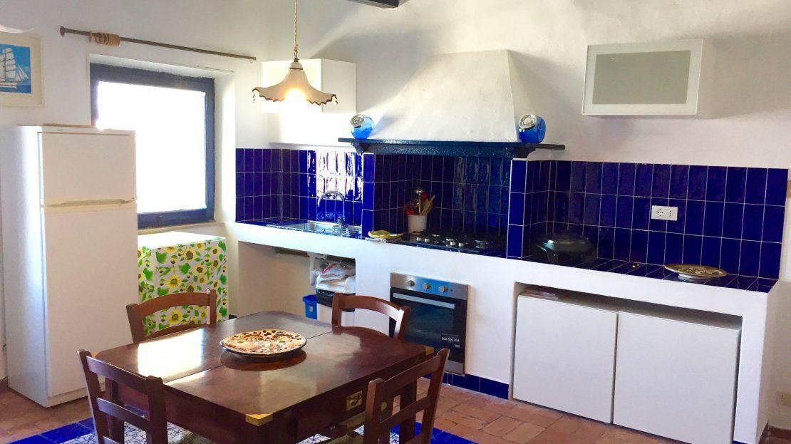 Cucina con tavolo piccolo in legno, 4 sedie ed angolo cucina con piastrelle blu