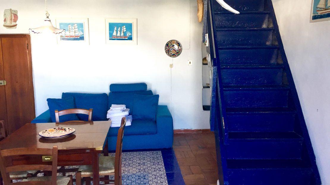 Tavolo da cucina con 3 sedie, divano blu e scale di accesso al piano superiore di colore blu