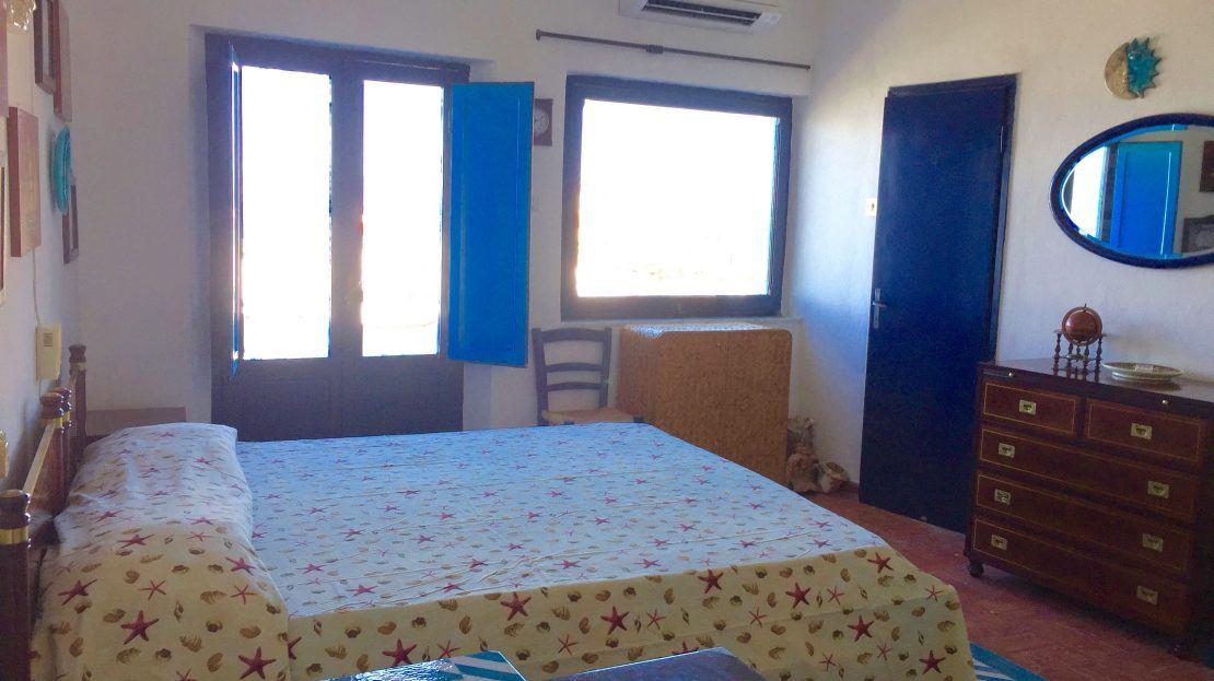 letto matrimoniale con fantasie marine e camera di pareti bianche, con doppia finestra, mobiletto in legno e porta di ingresso blu