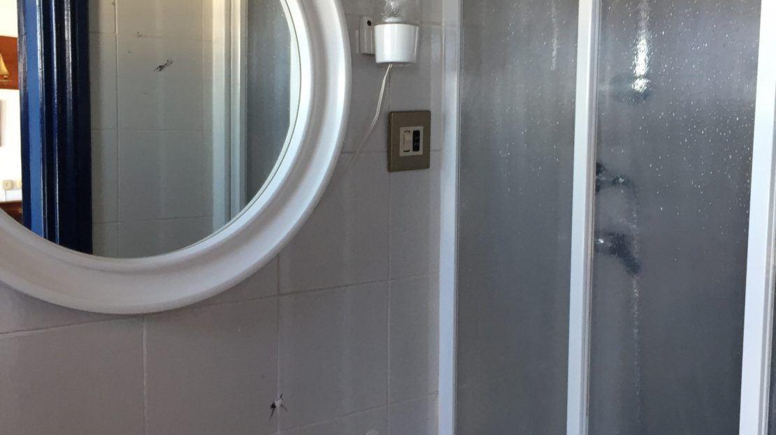 Bagno con lavandino, specchio circolare e box doccia in appartamento all'Isola del Giglio