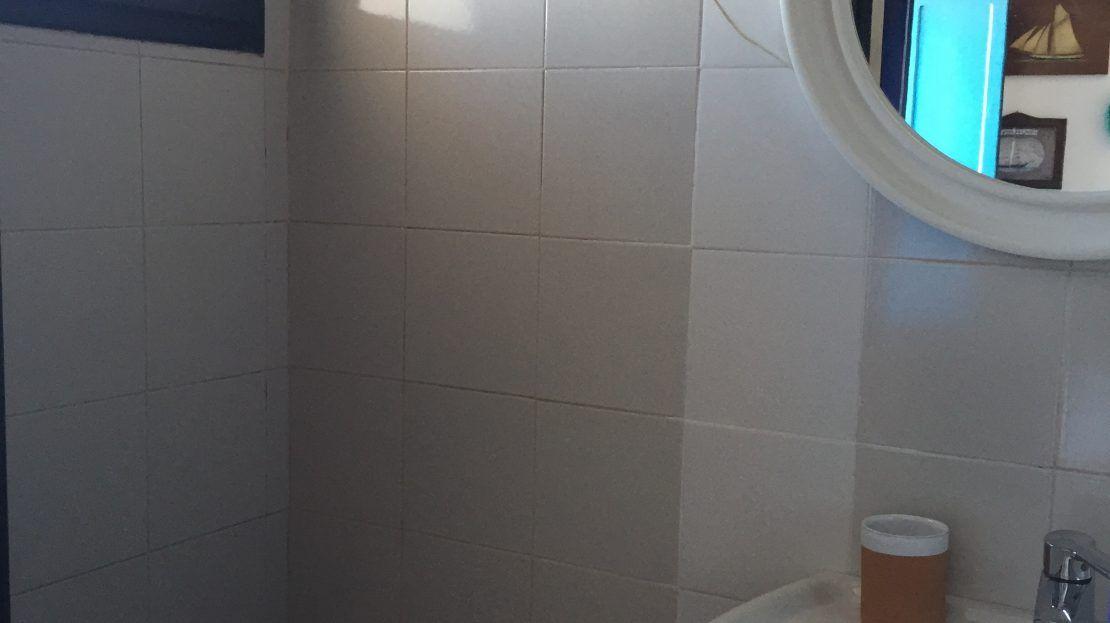 Particolare di bagno con lavandino, specchio circolare e wc, con mattonelle bianche