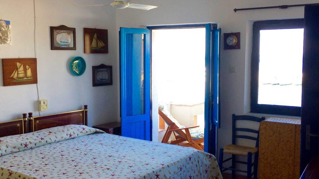 camera matrimoniale con letto matrimoniale, tappeto grande variopinto e finestra spalancata di color blu