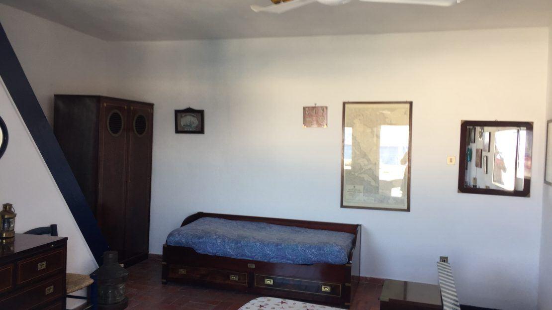 Particolare di camera da letto matrimoniale con letto, divanetto e mobile in legno, più 4 quadri appesi