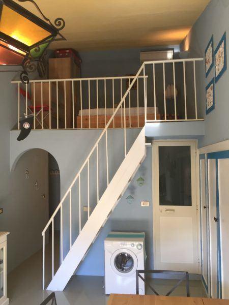 Scale con soppalco e lavatrice al piano inferiore in appartamento in vendita a Giglio Castello di recente ristrutturazione