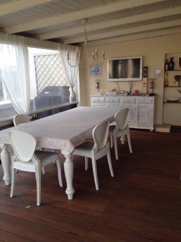 Sala da pranzo con tavolo apparecchiato e sedie presso attico in vendita a Grosseto, zona Stadio Carlo Zecchini