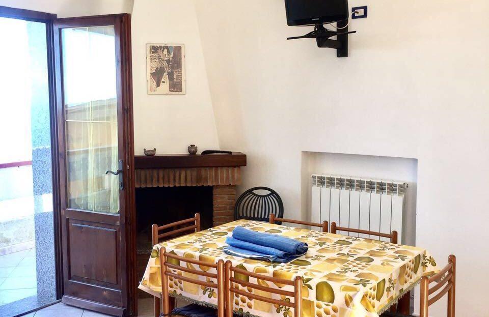 tavolo da cucina con 6 sedie in legno, all'interno della zona cucina del bilocale. Porta finestra di colore marrone aperta