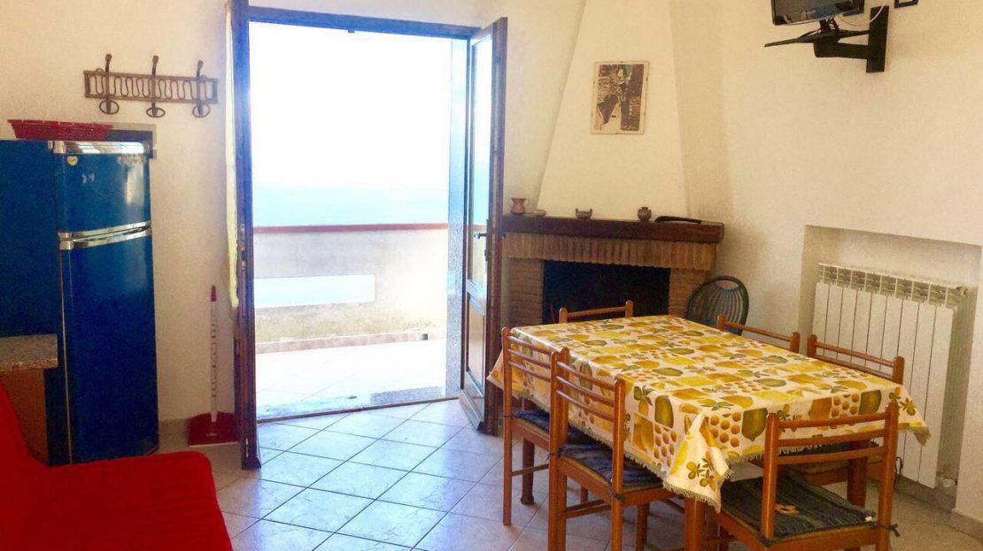 zona cucina con tavolo, sedie, camino, TV appesa e porta finestra aperta che da sul terrazzo