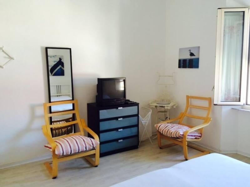 Porzione di camera da letto con sedie in legno, comodino e tv nel bilocale Giorgio in affitto a Giglio Porto