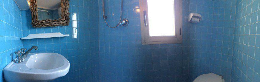 Foto di insieme del bagno con piastrelle blu presso il bilocale Lucrezia in affitto a Giglio Porto