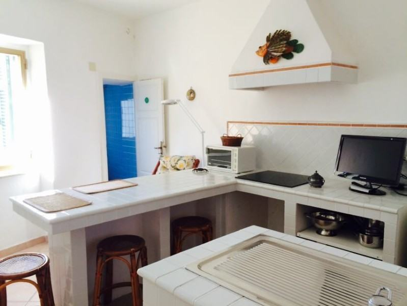 Parte della cucina con isola, e in lontananza porta che apre al bagno con mattonelle azzurre