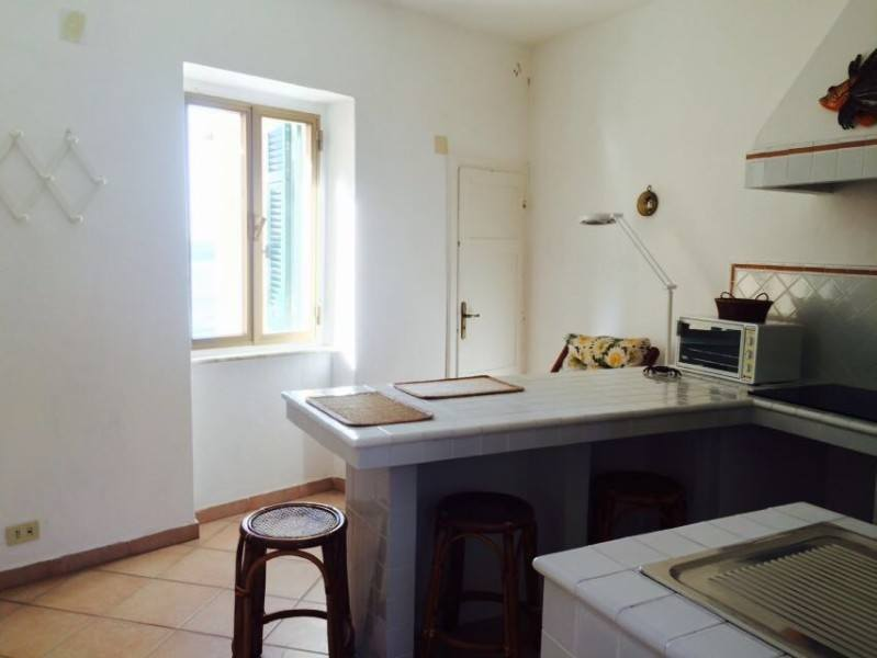 cucina con particolare dell'isola di colore bianco e parete anch'essa di colore bianco