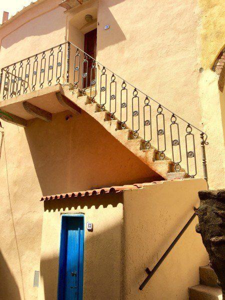 Facciata esterna color marrone, appartenente ad un bilocale con porticina azzurra e scalette di ingresso al piano superiore