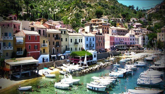 vista panoramica di Giglio Porto con case colorate e barche ormeggiate di fronte
