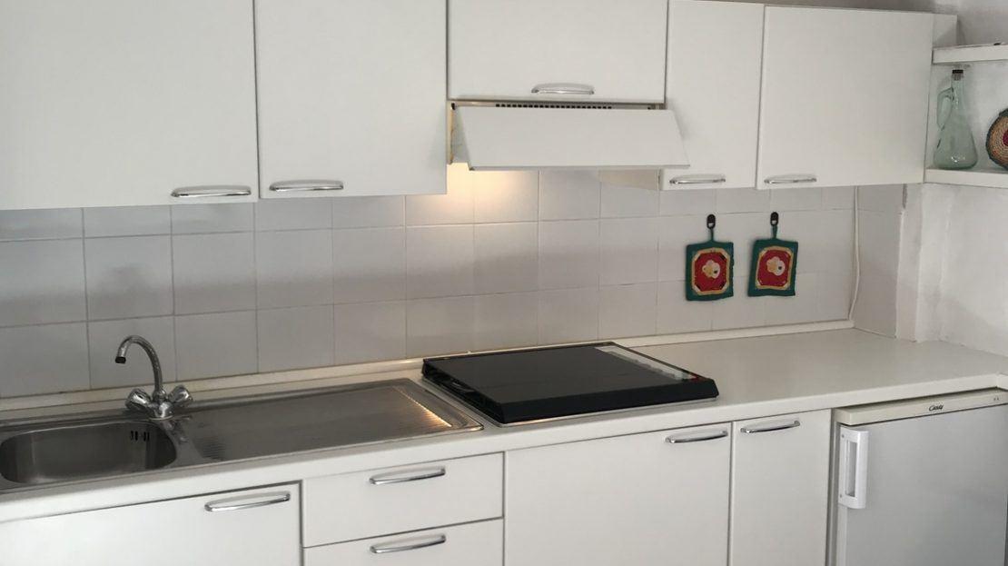 cucina di colore bianco con 2 presine colorate appese