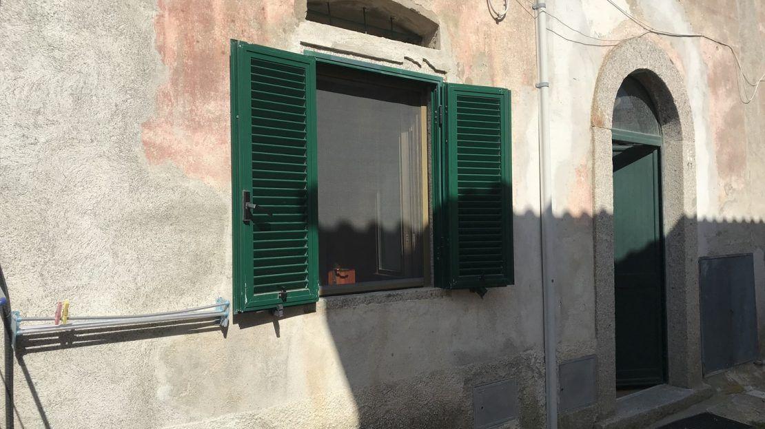 facciata esterna di monolocale con porta di ingresso e finestra aperta con persiane verdi