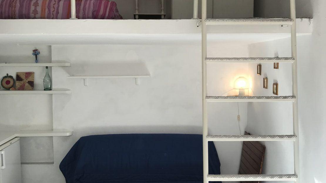 area interna monolocale con divano blu e zona soppalco con accesso portato da scalette bianche