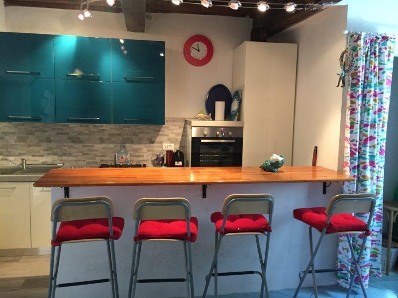 Piccola isola cucina con tavolo in legno e 4 sedie rosse presso un appartamento monolocale in affitto a Giglio Porto