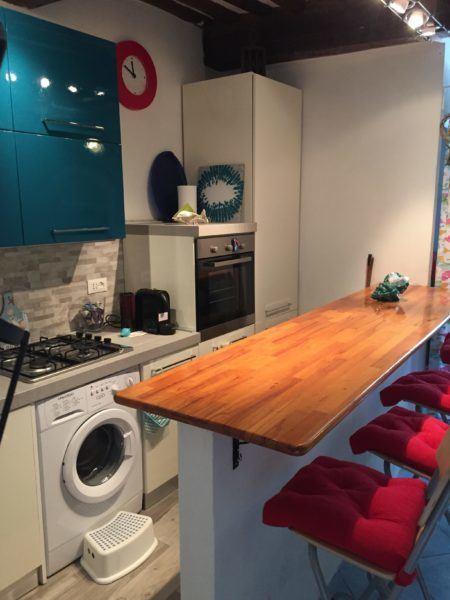 Angolo cucina con piccola isola in legno presso appartamento monolocale in affitto a Giglio Porto