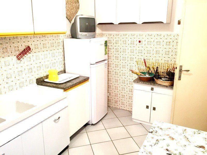 cucina con arredamento di colore bianco e piccolo televisore sopra il frigorifero