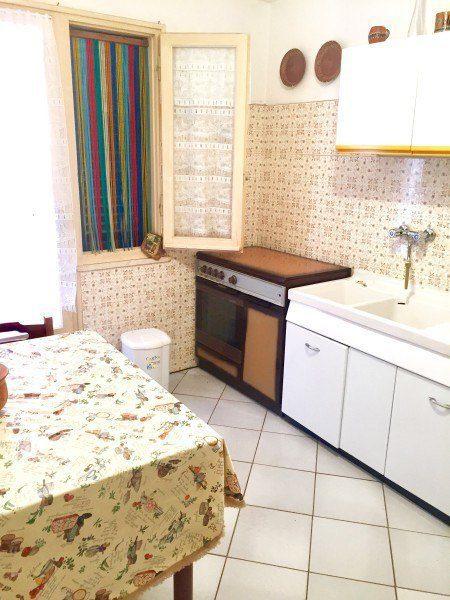 cucina con parte del tavolo e degli elettrodomestici. Finestra aperta con tendina variopinta