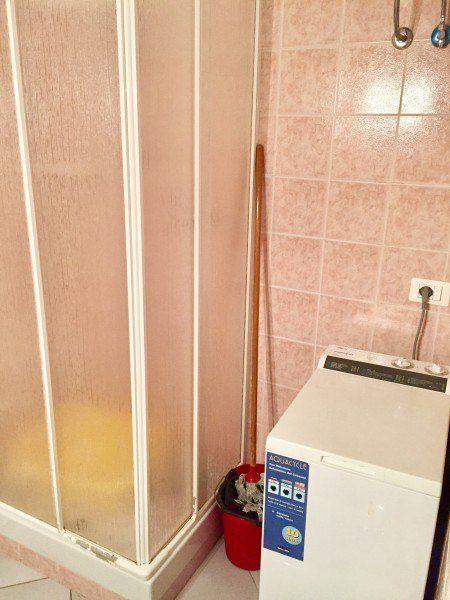 particolare del bagno con lavatrice e box doccia, più cencio per pulire di colore rosso