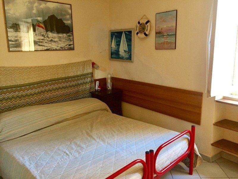 camera matrimoniale con letto matrimoniale con bordo metallico di colore rosso. 3 quadri appesi ed un piccolo salvagente