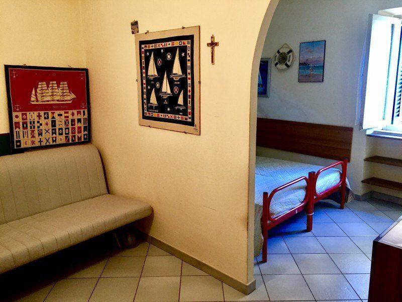 parte di un letto matrimoniale e parte di un divanetto con vari quadri appesi ed un piccolo crocifisso