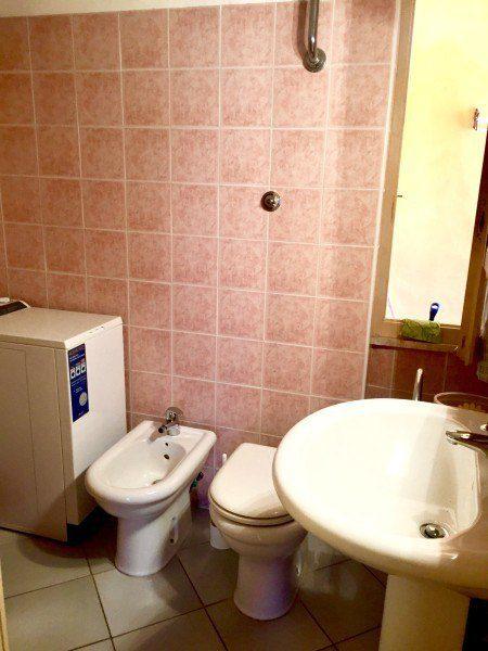 parte di bagno con piastrelle rosa, lavatrice, lavandino, wc. e lavabo