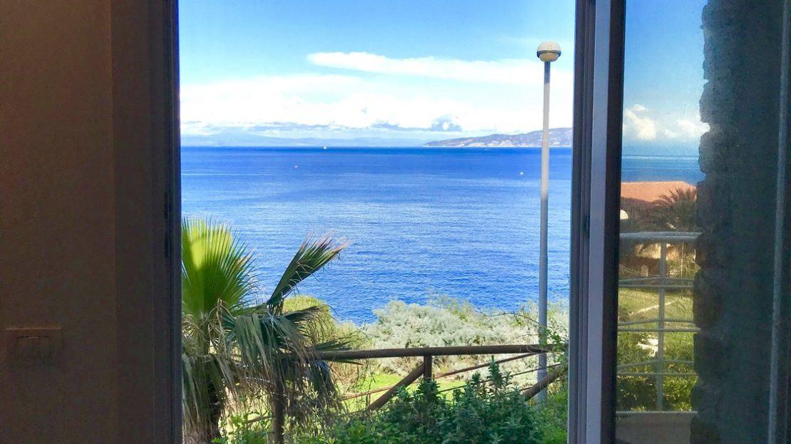 Finestra aperta con vista sul terrazzo e sul mare di Isola del Giglio