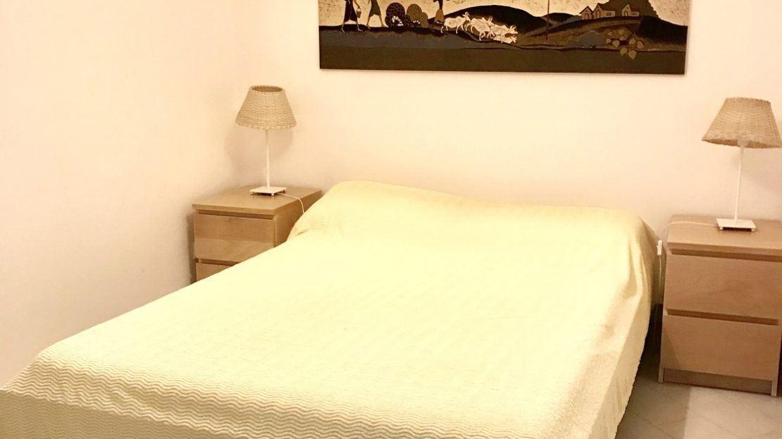 Letto matrimoniale con lenzuolo bianco, comodini marroni, lampade e quadro rettangolare appeso alla parete