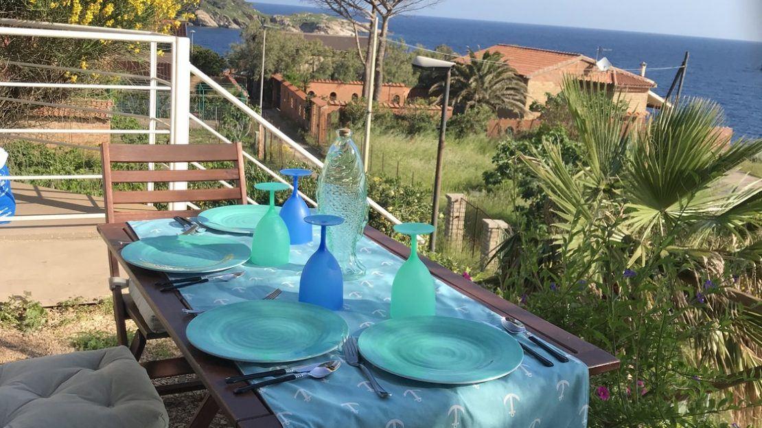 Tavolino apparecchiato con piatti e bicchieri di color turchese e blu presso terrazzo di trilocale