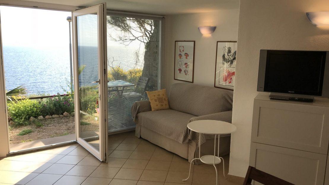 sala interna con mobilia di color bianco e finestra che da su terrazzo con vista del mare del Giglio