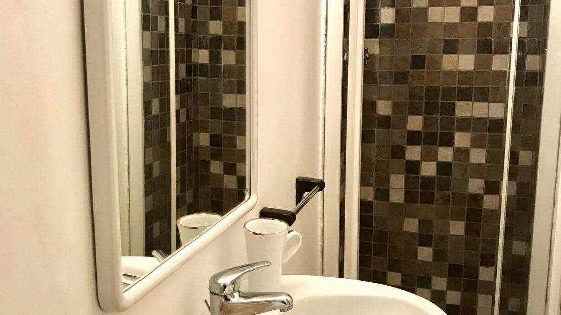 bagno con lavandino, specchio e box doccia con piastrelle mosaico