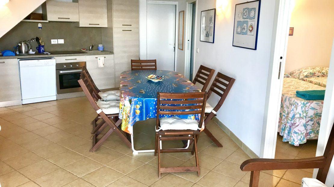 tavolo da cucina con 6 sedie in legno in area cucina, più parziale vista di 2 letti singoli in camera separata