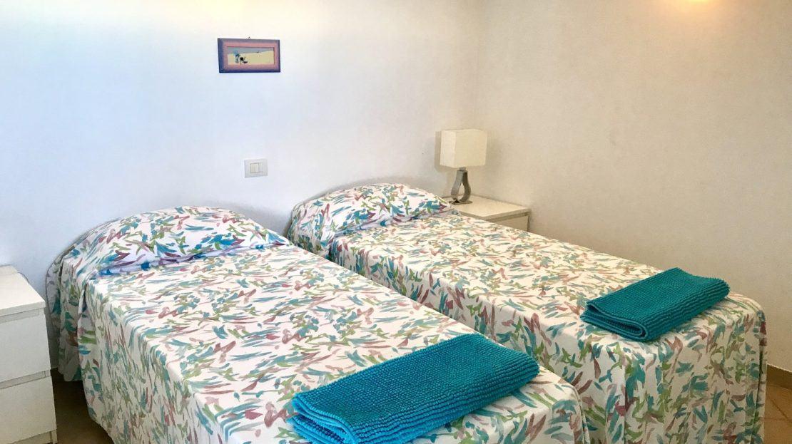 letti singoli con asciugamani color turchese presso camera da letto