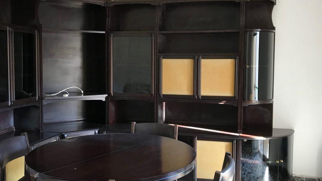 Mobili, tavolino e sedie di color nero all'interno di un trilocale in vendita a Giglio Porto