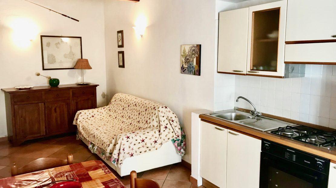 Angolo cucina e divano nell'appartamento Violetta disponibile in affitto nella località di Giglio Porto